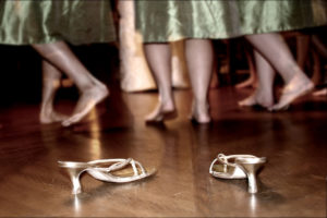 Three bridesmaids kick off their shoes to dance at a wedding reception