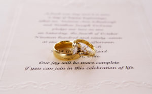 picture of a wedding invitation with wedding rings on top